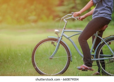 hands holding on bike handle on vintage bicycle on the blurred background of fresh greenery
