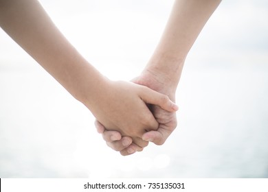 Hands holding on a white background, Close up.