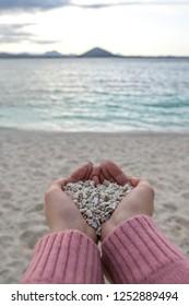 Hands holding on to white pebbles in Udo Sanho Beach or Seobinbaeksa in Jeju Island, South Korea