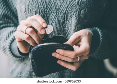 Hands holding one euro coin and small money pouch. Toned picture