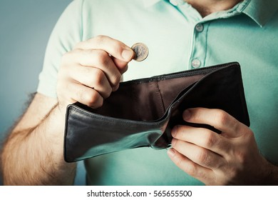 Hands holding one euro coin and an empty wallet. Concept of lack of money. close-up. on blue background