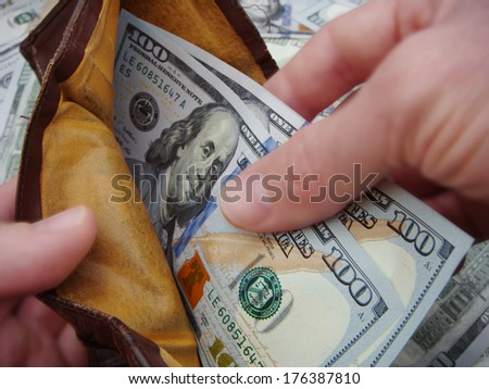 Hands Holding Open A Very Used And Worn Leather Wallet Holding Brand New United States One Hundred Dollar Federal Reserve Notes.