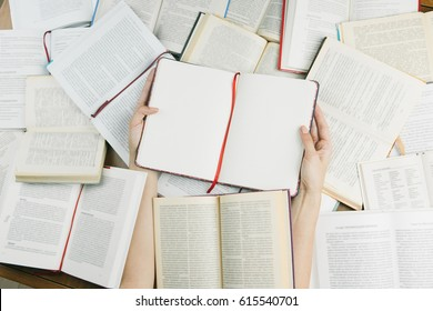 Hands holding opened notebook Among many books. Top view. Get lost in the information. A lot of knowledge