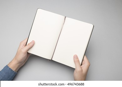 Hands holding opened notebook, blank paper Mock-up.