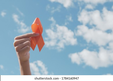 Hands holding orange Ribbon over blue sky,  Leukemia cancer and Multiple sclerosis, COPD and ADHD awareness, world kidney day