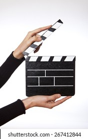 Hands holding out a clapper bord on white background