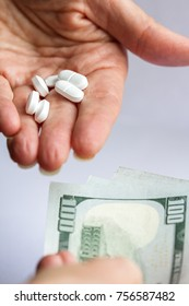 hands holding pain killer prescription opioids and another hand handing over three hundred US dollar bills