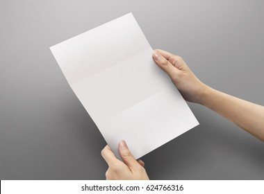 Hands holding paper blank a4 size for letter paper on grey background