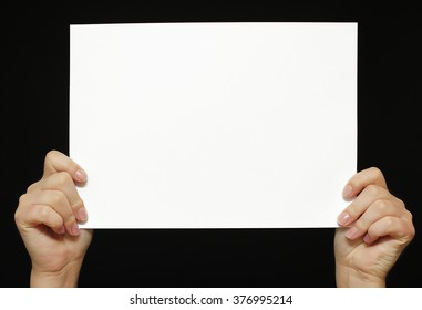 Hands holding paper blank isolated on black background