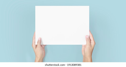 Hands holding paper blank for a letter paper