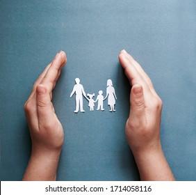 manos sosteniendo el corte familiar de papel, concepto de distanciamiento social, covid19 sobre el fondo de color azul