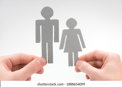 Hands holding paper figurines of man and woman on white background. Selective focus on male figure. Concept of gender inequality.