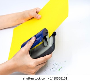 Hands holding paper hole puncher of office stationery and punching paper on white background