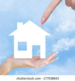 Hands holding a paper Home on sky blue background