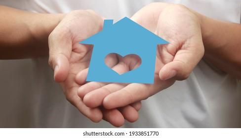 Hände, die Papierhaus, Familienwohnungen und Versicherungsschutz halten