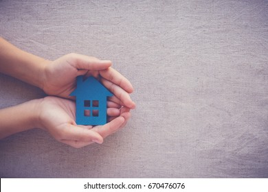 hands holding paper house, homeless shelter and real estate concept