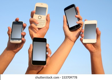 hands holding phones with blue sky as background