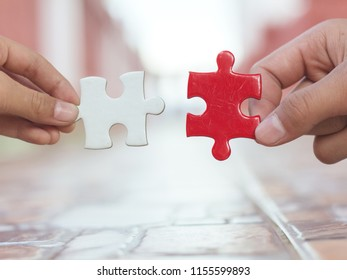hands holding piece of gold and red jigsaw puzzle