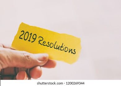 Hands holding piece of paper with text - 2019 Resolutions.