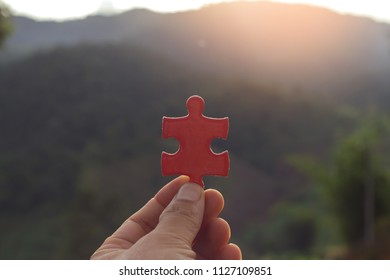 hands holding piece of red jigsaw puzzle
