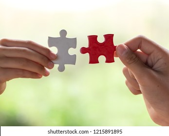 hands holding piece of red jigsaw puzzle. teamwork concept