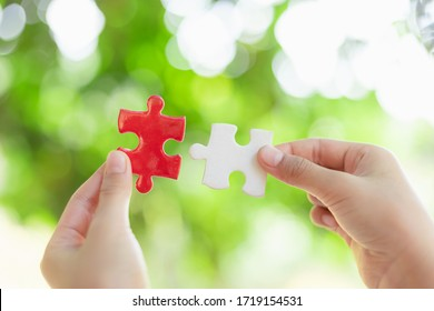 hands holding piece of red jigsaw puzzle on nature bokeh background. teamwork concept