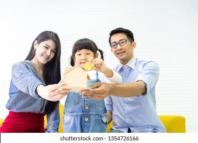 Hands holding piggy bank .Family saving money to wooden home bank. Pretty little girl and family putting coins into bank for dream house. Children, money, investments and people concept