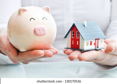 Hands holding a  piggy bank and a house model. Housing industry mortgage plan and residential tax saving strategy