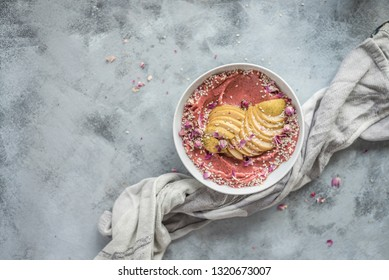 Hands Holding Pink Smoothie Bowl with Apples, Seeds & Flowers