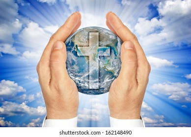 """Hands holding the planet Earth with the Christian cross .""""Elements of this image furnished by NASA"""""""