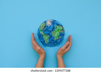 Hands holding planet Earth made from plastic disposable packages on blue background. Save the world, creative, environment pollution or World Earth Day concept. Top view