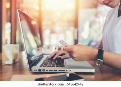 Hands holding plastic credit card and using laptop. buy online.