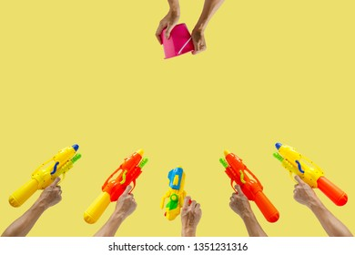 Hands holding plastic water gun and bucket ready to fight for Water or Songkran festival which celebrate in Thailand summer time on April with yellow color background.