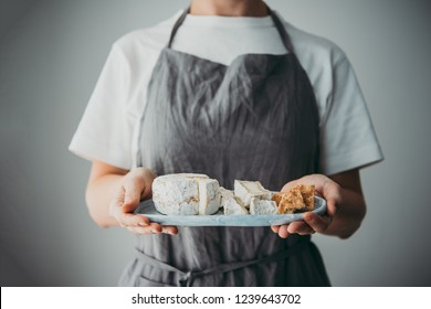 Hands holding a plate with cheese and crackers. Wine dinner or aperitivo party concept.