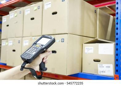 Hände, die tragbare Barcode-Scanner im Lager halten
