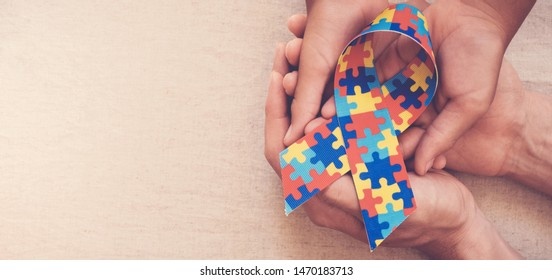 Hands holding puzzle ribbon for autism awareness banner
