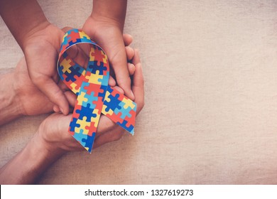 Hands holding puzzle ribbon for World Autism Awareness Day, pride, jigsaw