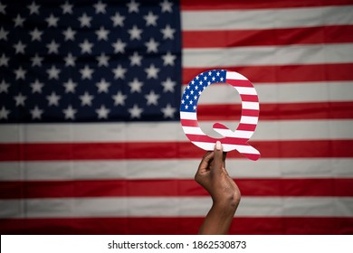 Hands holding Q alphabet with US flag as background with copy space - Concept QAnon or Q Anon deep state conspiracy theory