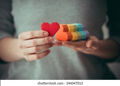 Hands holding  rainbow paper hearts, LGBT symbol. Toned picture