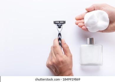 Hands holding razor blade and shaving foam, with after shave isolated  on white background, with copy space, top view. Shaving products for men.