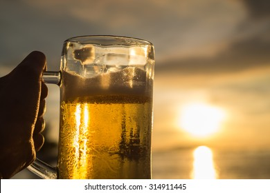 A hand's holding a really cold Beer in the mug with the sunlight shine on the sea background (Selective Focus Point)