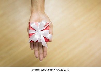 Hands holding red gift box on wood backgrounds