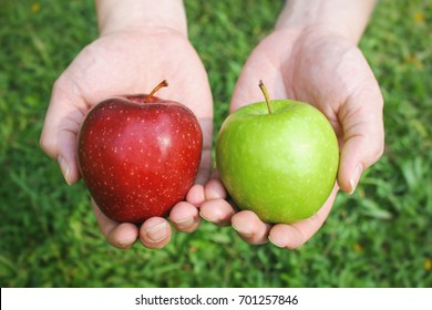 Hands holding red and green apples on green grass background with copy space
