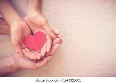 Hände, die rotes Herz halten, Herzgesundheit, Spende, fröhliche Freiwilligenwohltätigkeit, soziale Verantwortung der sozialen Verantwortung, Weltherztag, Weltgesundheitstag, Tag der psychischen Gesundheit, Heim fördern, Wohlbefinden, Hoffnungskonzept