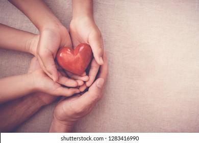 erwachsene und kinderreiche Hände, die rotes Herz halten, Organspende, glückliche Freiwilligenwohltätigkeit, Familienversicherung und CSR-Konzept, Weltherztag, Weltgesundheitstag, Tag der psychischen Gesundheit, Pflegekonzept