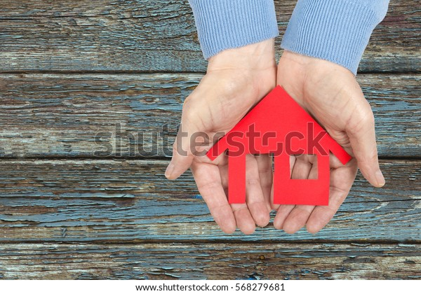 Hands Holding red paper house over wooden background