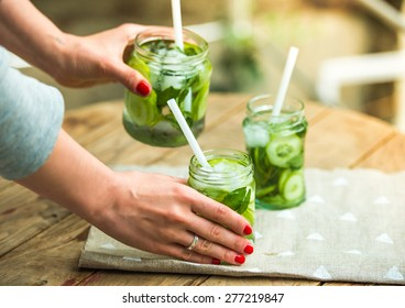 7538bdbef62 Hands holding retro glass jars of lemonade with cucumber and mint on wooden  table