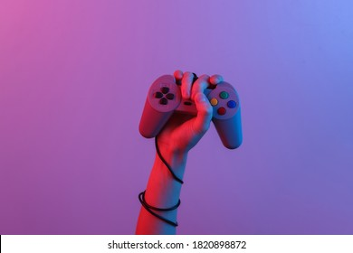 Hands holding retro joystick in blue-red neon gradient light. Old gaming. 80s retro wave. Minimalism
