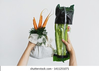 Hands holding reusable eco friendly bag with fresh carrots against celery in cellophane plastic package on white background. Zero waste grocery shopping. Ban plastic. Choose plastic free.
