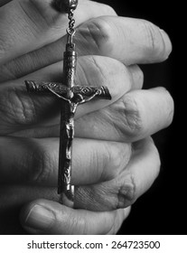 Hands holding a rosary in prayer